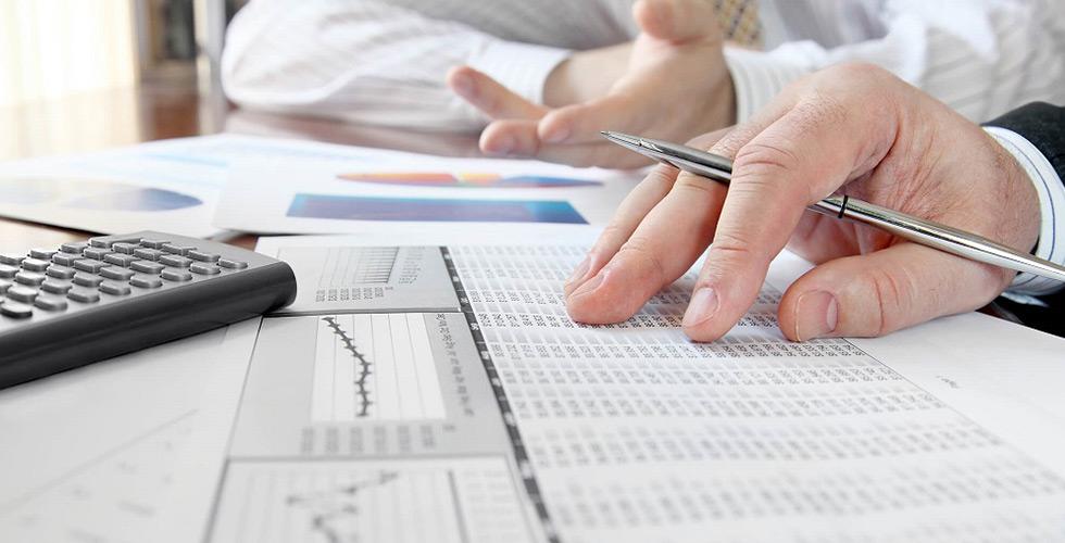 mãos sobre planilha e calculadora avaliam a gestão de custos de uma empresa