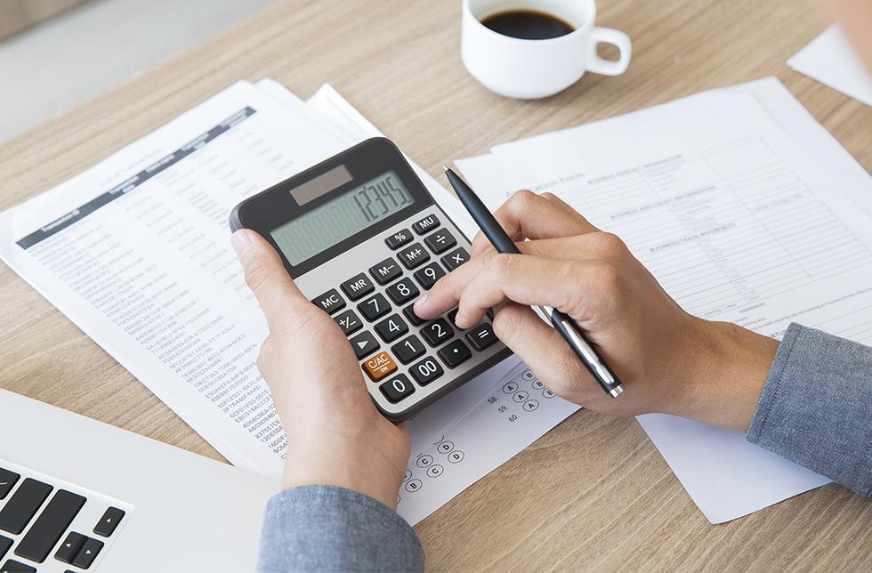 mãos seguram caneta e calculadora fazendo cálculo sobre tributação