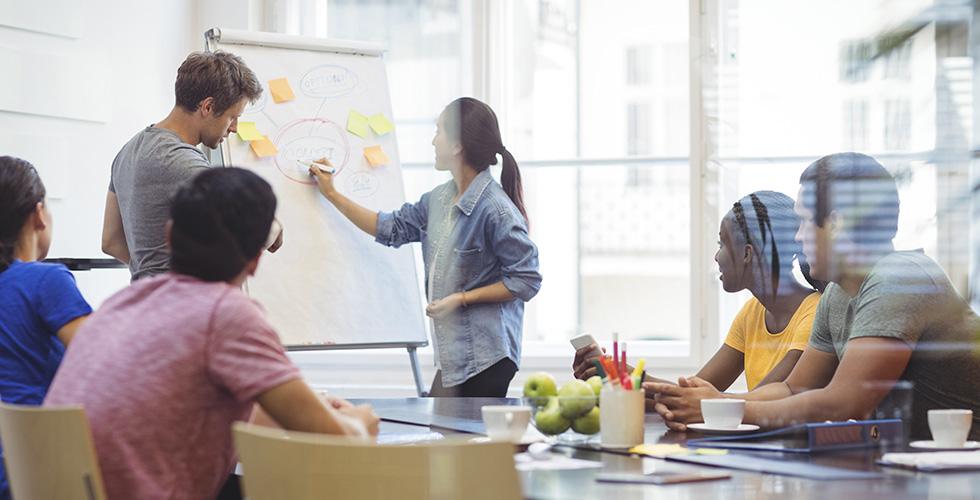 equipe em volta da mesa em reunião de ideias verifica as vantagens de um ERP integrado