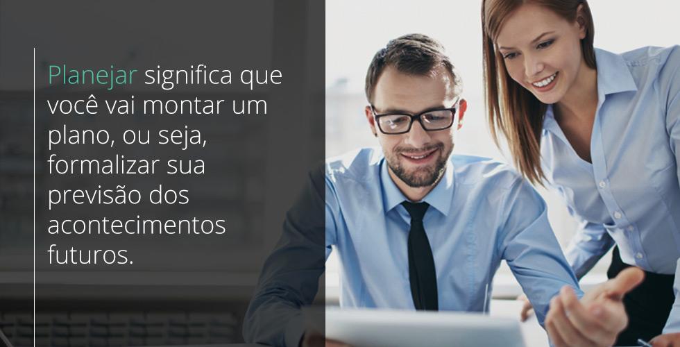 Homem sentado vestindo camisa azul e gravata preta olha para o tablet enquanto uma olhar fica ao seu lado em pé olhando para a tela do tablet, vendo informações sobre PPCP